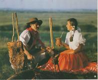 o gaúcho e sua prenda tomando um chimarrão e comendo um churrasco